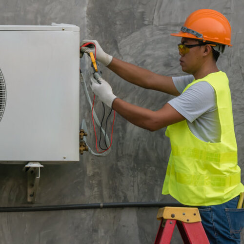 Technician working on an air conditioning unit.