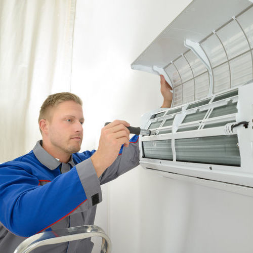 Technician Working on Air Conditioner Maintenance